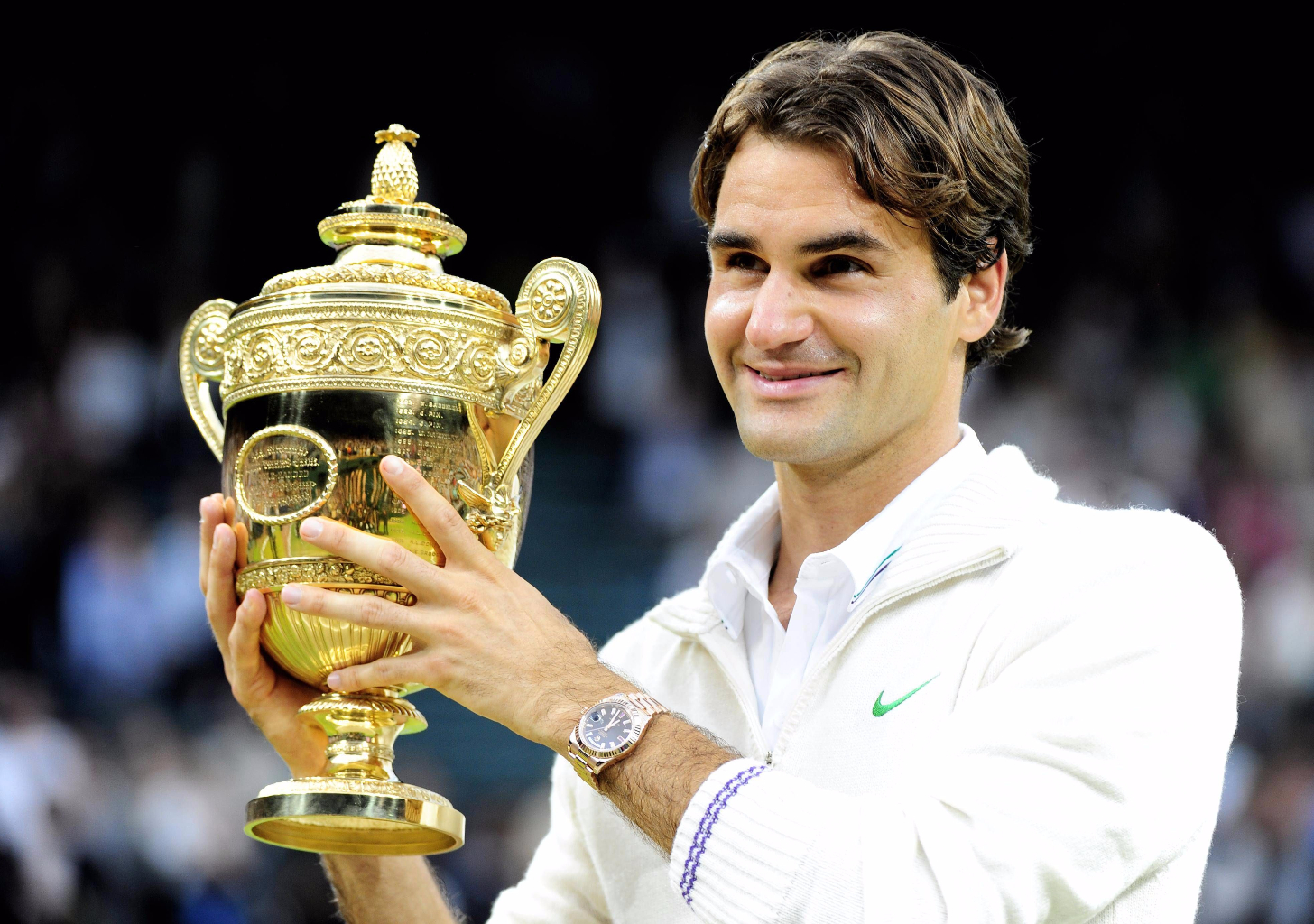 Switzerland's Roger Federer celebrates with his trophy after defeating Great Britain's Andy Murray in the Men's Singles Final during day thirteen of the 2012 Wimbledon Championships at the All England Lawn Tennis Club, Wimbledon. PRESS ASSOCIATION Photo. Picture date: Sunday July 8, 2012. See PA story TENNIS Wimbledon. Photo credit should read: Clive Rose/POOL/PA Wire. RESTRICTIONS: Use subject to restrictions. Editorial use only, including for mobile devices / apps and books. Commercial use only with prior approval. Call +44 (0)1158 447447 for further information.