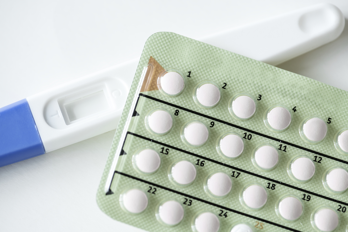 Closeup of pregnancy test and contraceptive pills birth control concept